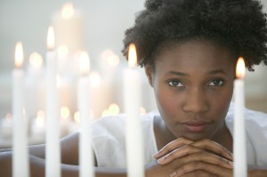 Woman Among Lit Votive Candles