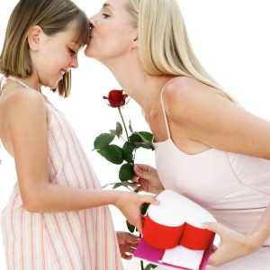 Mother Kissing Her Daughter for a Present and Red Rose